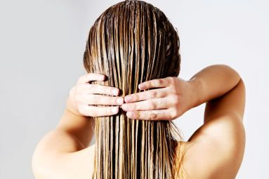 rear-view-of-woman-applying-conditioner-on-hair-against-white-background-691089397-588e50813df78caebc26cf1e